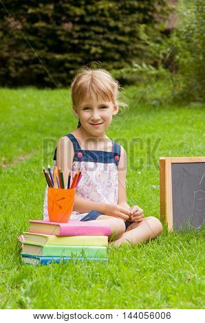 little schoolgirl getting ready for school in nature. early childhood development
