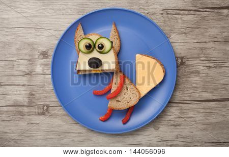 Squirrel made of bread and vegetables on plate and desk