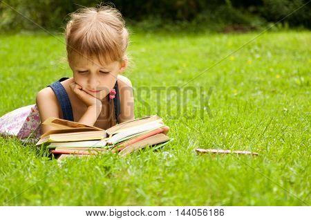Little schoolgirl is reading a book. smart little pupil