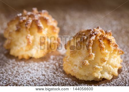 Coconut macaroons christmas cookies with powdered sugar on wooden background