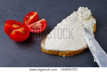 Bread with butter knife and tomato on a dark background close-up.