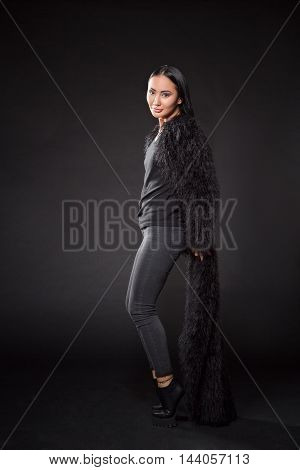Beautiful brunette lady posing in full length over dark background. Lady with long black hair looking at camera.