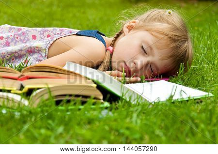 Little girl tired of reading and she fell asleep