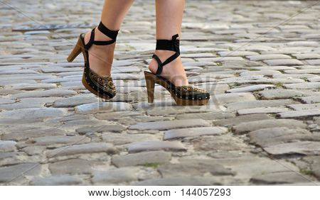 girl in stylish fashion footwear is on the sidewalk in the city