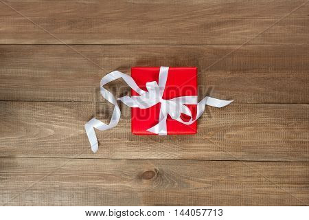Beautifully packed gift lies on a wooden table