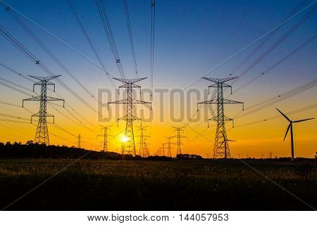 the sun sets behind the lines of hydro towers with one lonely windmill on the side in the Southern Bruce Peninsula.