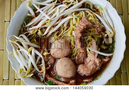 Chinese noodle with pork ball in brown soup on bowl