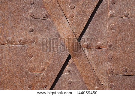 A fragment of an ancient metal surface with rivets. Texture background