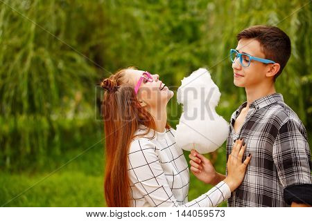 Enamoured teens eat cotton candy. Girlfriend and boyfriend together. They wear glasses. First love. He falls in love. Date.