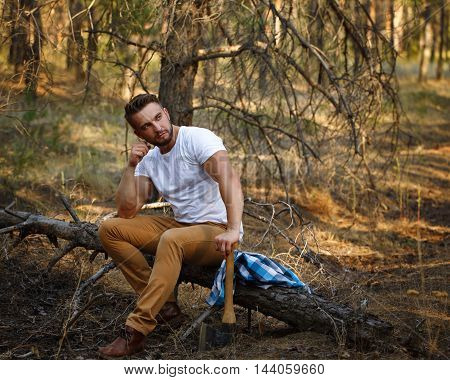 Lumberjack sat down with an ax on a fallen tree. Woodcutter in a white T-shirt. Felling trees. Logging. Manual labor.