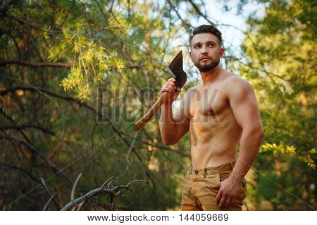 Lumberjack holds a cleaver. Woodcutter with naked torso in the coniferous forest. Felling trees. Logging. Manual labor.
