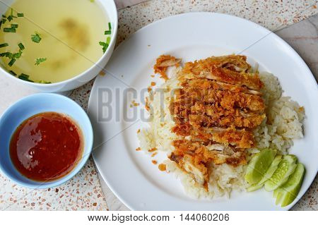 fried chicken on steamed rice with sweet chili sauce and soup