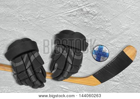 Finnish hockey puck stick and gloves on the ice arena. Concept