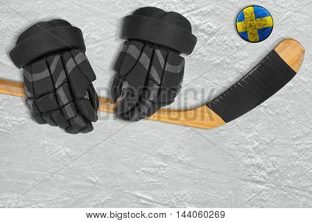 Swedish hockey puck stick and gloves on the ice arena. Concept