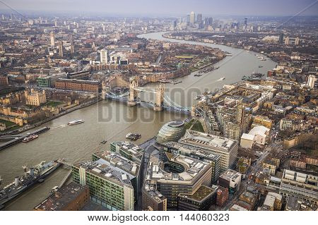 London England - Aerial Skyline view of London with the world famous Tower Bridge Tower of London and skyscrapers of Canary Wharf on a cloudy afternoon