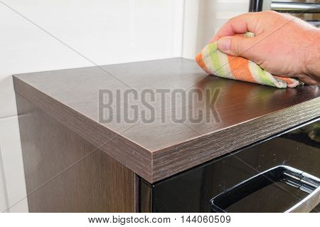 Wiping a dusty cabinet with wooden surface with a cleaning cloth.