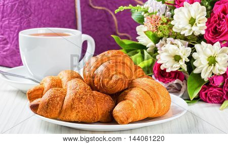 French croissants on white dish cup of tea and bouquet of fresh flowers on old wooden boards beautiful box wrapped in paper and decorated with ribbon on background close-up selective focus