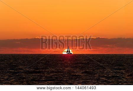 sailboat sunset silhouette is a boat sailing with full sails out silhouetted against a white hot setting sun and a bright orange cloudscape hovering overhead.