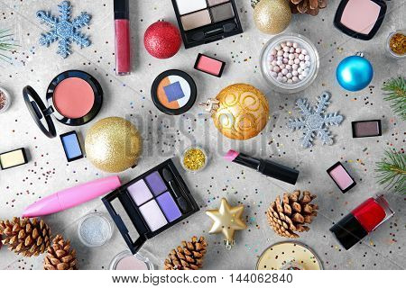 Makeup products and Christmas decorations on color background