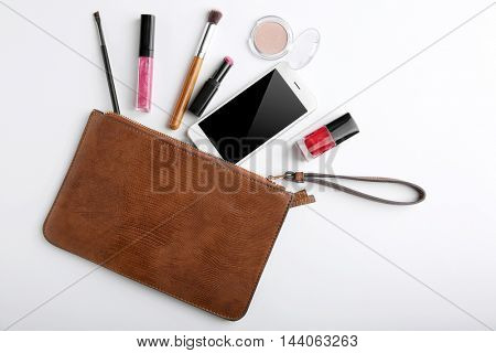 Makeup bag with beauty products and phone on white background