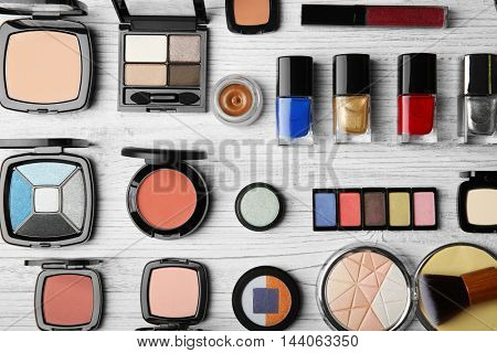 Cosmetic products and brushes on wooden background