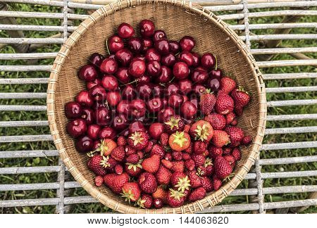 ripe strawberries and cherries in a round basket