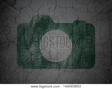 Tourism concept: Green Photo Camera on grunge textured concrete wall background