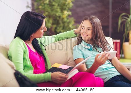Woman using laptop in living room while her daughter using smart phone