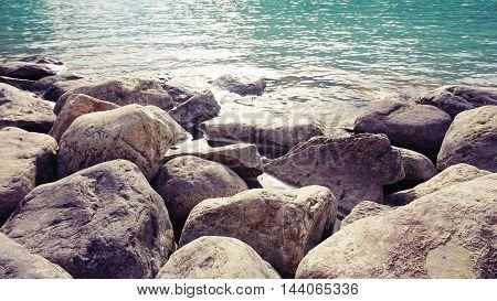 beautiful lake clear blur water and rocks retro filter