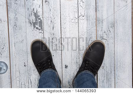 Footwear concept. Top view of men's winter boots of black colour. Man making photo of his fashionable boots isolated on wooden.