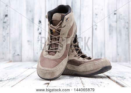 Footwear concept. Men's winter boots represented on wooden background are nice idea for spending winter holidays in snow weather.