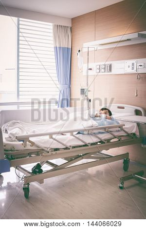 Illness asian boy sleeping at modern and comfortable equipped hospital room with infusion pump intravenous IV drip. Health care and people concept. Vintage tone effect.