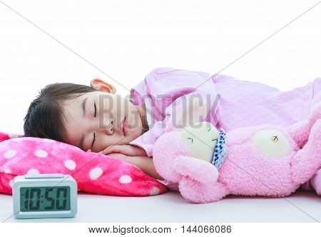 Healthy children concept. Asian child with doll sleeping peacefully. Adorable girl in pink pajamas sleep tight with alarm clock in foreground. On white background.