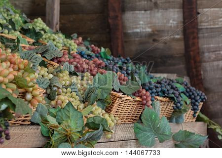 Bunch Of Colorful Grapes In Wicker Basket On Wooden Shelf