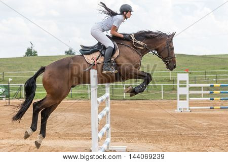 SVEBOHOV CZECH REPUBLIC - AUG 20: Side view of beautiful longhaired horsewoman jumping on a brown horse at