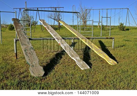 Three  wooden teeter totters on a school yard playground with swing sets in the background.