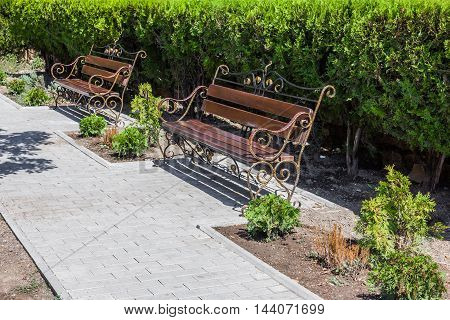 benches standing along the sidewalk and green bushes