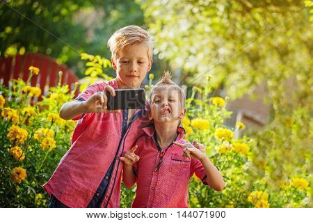 Best friends. Two cute little boys doing selfie and making funny faces outdoors