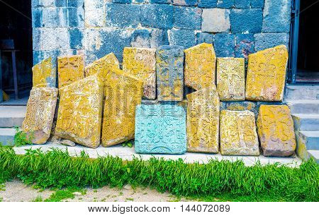 The old ruined khachkars acquired various colors because of the lichen and moss covering them for the years Sevanavank Monastery Sevan Armenia.