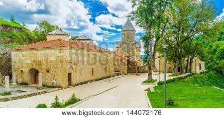 The St Astvatsatsin Church with the high stone dome and renovated Refectory building on the foreground Haghartsin Monastery Armenia.