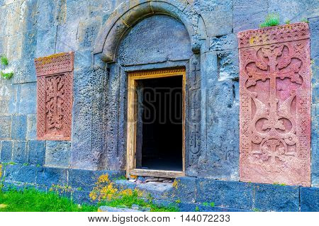 The red khachkars built in the black facade wall around the entrance to the Hayravank Monastery Armenia.