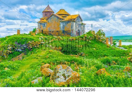 The juicy green hill with bright orange boulders covered with lichen and moss topped with the Church of Hayravank Monastery and its small cemetery Armenia.