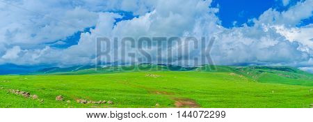 The fluffy clouds lies on the gentle highlands of Gegharkunik Province surrounded by juicy wet meadows Armenia.