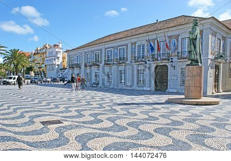 CASCAIS PORTUGAL - MAY 1 2012: The Camara Municipal (Town Hall) decorated with azulejos (portuguese tiles) located on Outubro Square with traditional paving stone pattern and monument to Dom Pedro I on May 1 in Cascais.