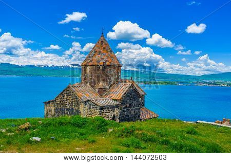 The Surp Arakelots (Holy Apostles) Church of Sevanavank Monastery with the Sevan Lake and snowy mountains on the background Sevan Armenia.