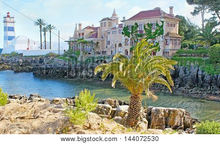 The tiny rocky bay is the nice place to walk and enjoy the historic Villa of Santa Maria and beautiful Santa Marta lighthouse Cascais Portugal.