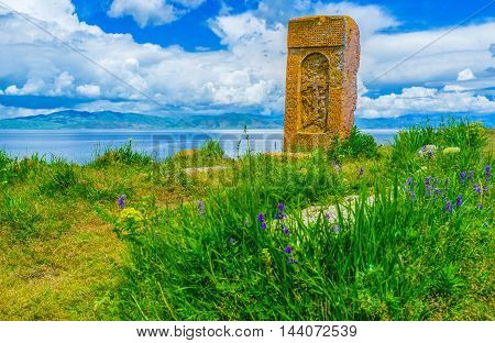 The khachkar (cross-stone) on the hilly meadow among the wildflowers with the cloudy mountains and Sevan Lake on the background Hayravank Armenia.
