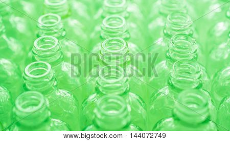 Number empty glass bottles on conveyor, green tone