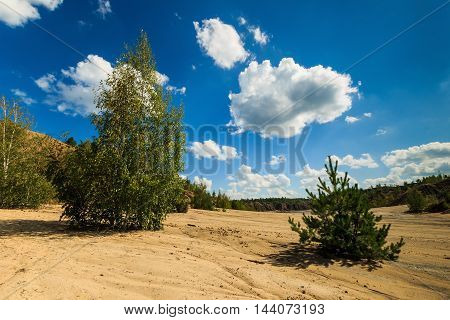 Quarry With Sandy Beach,trees And Hills With Cloudly Sky