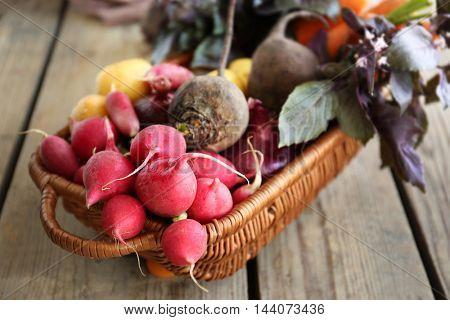 Wicker basket with fresh vegetables on wooden background
